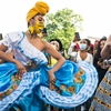 Two Black women in colorful dresses dance in front of a crowd to celebrate Juneteenth.