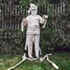 A person in a mummy costume posing in front of an overgrown fence.
